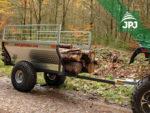 Transport längerer Holzstücke auf dem Anhänger Farmer